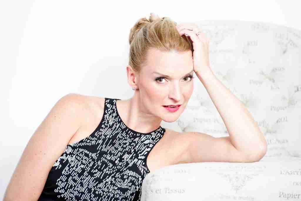 Andrea Powell seated black dress white beading